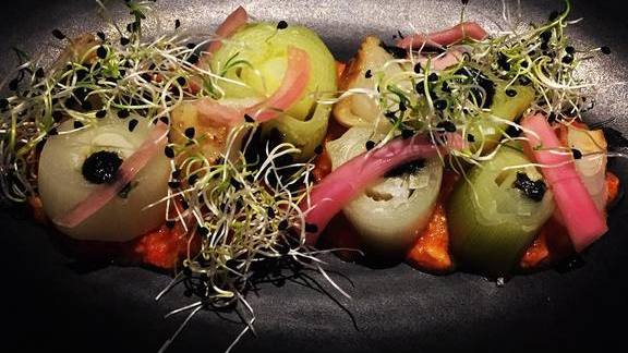 Chef Ted Hopson reviews Romesco, braised leeks, charred leeks, roasted cippolini, pickled red onion, onion sprouts at The Bellwether