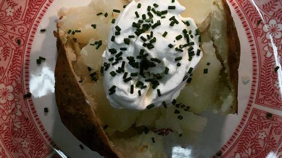 Baked potato with crisped skin, sour cream and chives at Alfreds