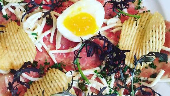 Beef carpaccio with potato crisps, greens, sprouts and runny egg at Foreign Cinema