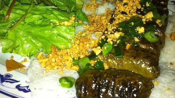 Grilled ground beef wrapped in grape leaves at Nam Phuong