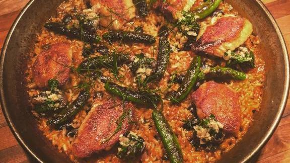 "New ""Valencian"" paella with crispy boneless confit chicken wings, braised snails & beans, and charred snap peas at Bellota"