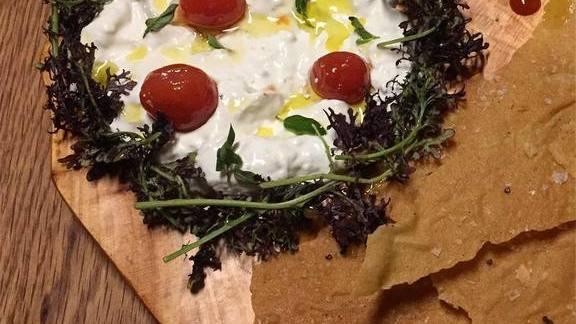 Chef Silvia Barban reviews Stracciatella, cherry tomato confit, red mustard greens, pan carasau at LaRina Pastificio & Vino