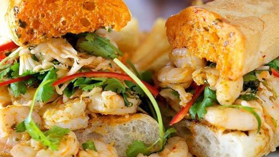 Shrimp Caminada po boy in spicy citrus butter with Asian slaw and fresh herbs at Grand Isle Restaurant