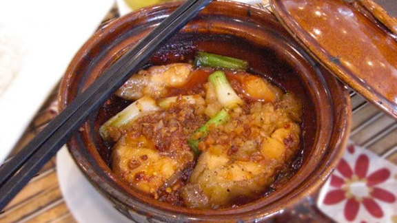 Chef Nicole Pederson reviews Catfish simmered in a clay pot at