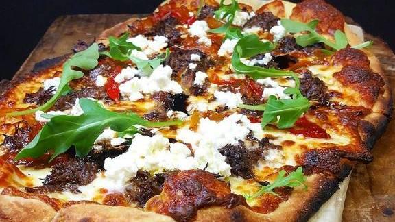 Pizza with mozzarella cheese, ricotta, peperonata, arugula, and short ribs at Farm Shed Dinners