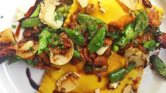 Bell pepper and goat cheese Raviolo with Hedgehog mushrooms, pea purée and marcona almonds at Little Bird Bistro