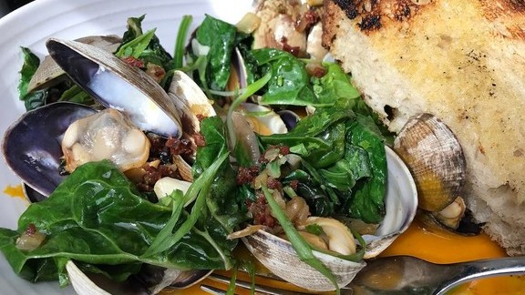 Manila clams with tomato confit, Swiss chard, chorizo, and grilled toast at The Larder at Maple Drive