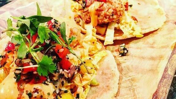 Tacos with coconut shrimp, mango-ginger pico, sesame-siracha slaw at American Kitchen and Bar