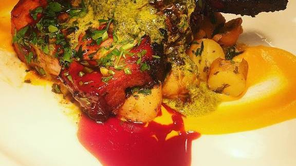 Pork chop with carrot purée, potatoes, chimichurri, and red wine sauce at Brasserie Beck