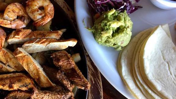 Shrimp and chicken fajitas with corn tortillas, purple cabage, guacamole and tomato at Araña Taqueria Y Cantina