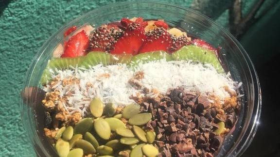 Acai bowl with pumpkin seeds, coconut, cacao nibs and strawberries at Huriyali Gardens