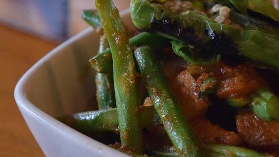 Green bean and potato vindaloo curry with black eyed peas and grilled shishito peppers at Mana Food Bar