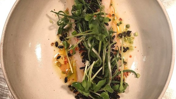 Hamachi crudo with confit egg yolk, puffed black rice, radish sprouts and a citrus soy vinaigrette at Tiger Mama