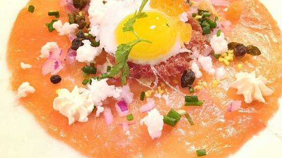 Chef Robert Wiedmaier reviews Smoked salmon carpaccio, shaved red onion, crispy capers, brioche crouton, sunny-side-up quail egg, smoked trout roe at