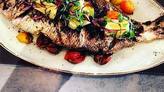 Whole roasted fish with cherry tomatoes at Herringbone Las Vegas