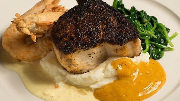 Blackened swordfish with sautéed spinach, fried shrimp, mashed potatoes, chili hollandaise and corn butter at GW Fins