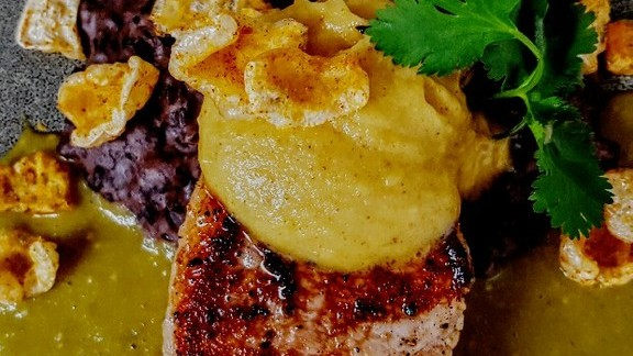 Chef Rio Miceli reviews Island pork rib chop, chili verde, mango-browned butter, turtle bean mash and chicharones at Copper Bar