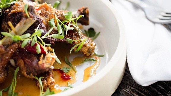 Duck confit wings, Pierre Ferrand orange amères glaze, Calabrian chili and cilantro at The Douglas Room