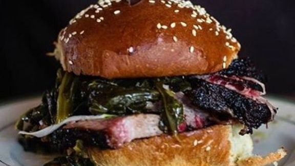 Smoked brisket, braised greens, and red onion on a milk bun at Smokehouse Tavern