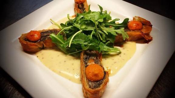 Mushroom strudel with romesco sauce, mustard cream, arugula, and lemon vinaigrette at Mother's Bistro & Bar