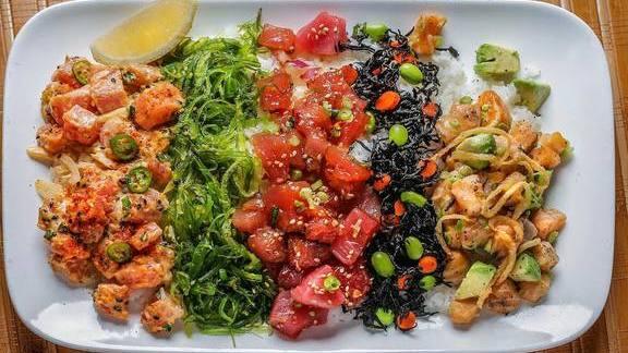 Poke Chirashi, with Original Ahi, Salmon Avocado and Spicy Serrano Poke, wakame salad, Hijiki salad, cucumber, daikon sprout salad on warm seasoned short-grain rice at Pacific Catch