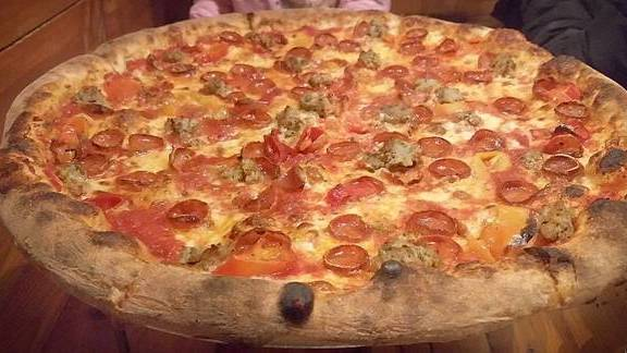 Pepperoni, sausage, cheese and tomato pizza at Apizza Scholls