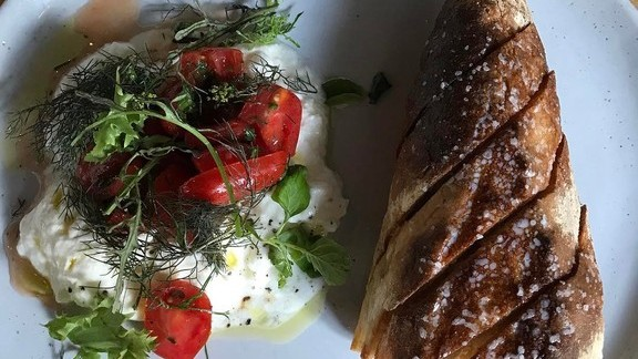 Baguette with burrata, tomato, basil and dill at Emmer & Rye
