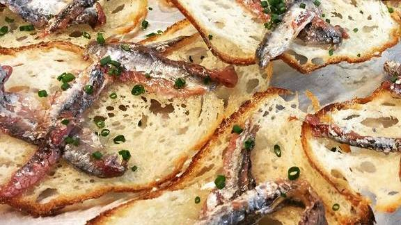 Chef Jason Ryczek reviews Italian anchovies on sourdough toast at Farallon