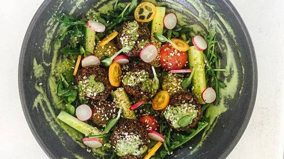 Chef Scott Winegard reviews Sprouted garbanzo, fava, pea falafel, tahini, wild arugula and lambs quarters at Plant Food + Wine Miami