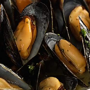 Steamed mussels with collard greens and crispy grit crackers at Boucherie