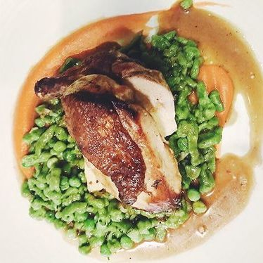 Pan Roasted Mary's Chicken with spinach spaetzle, spring onion, english peas, smoked carrot puree & roasted chicken jus at Akasha