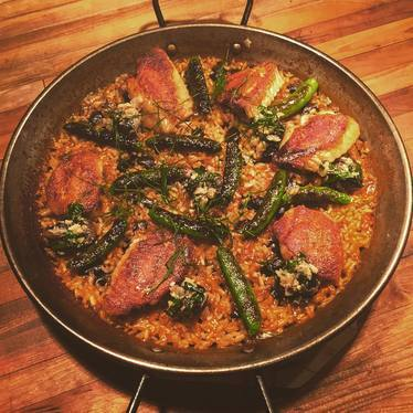 """New """"Valencian"""" paella with crispy boneless confit chicken wings, braised snails & beans, and charred snap peas at Bellota"""