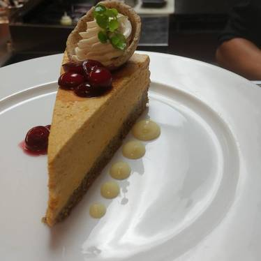 Pumpkin cheesecake with white chocolate, grains of paradise crust, braised cranberries at The Forge