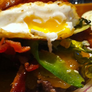 Single cheeseburger with jalapeños, bacon and fried egg at Stackhouse Burgers