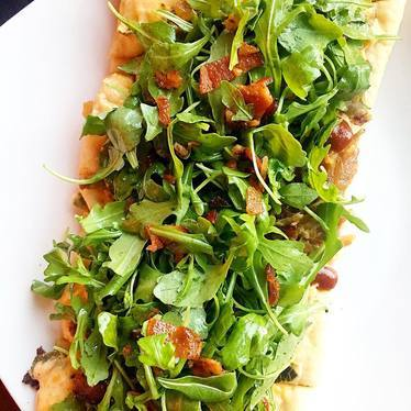 Vegetarian flatbread with bacon and arugula at HŌM