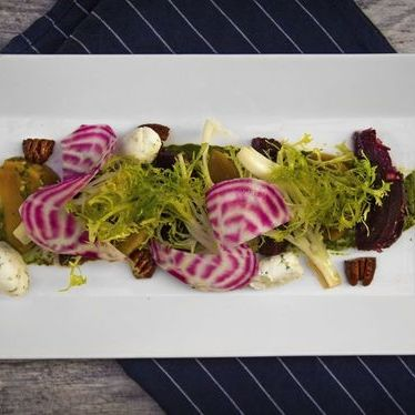 Beet salad with greens, herb pesto, goat cheese, candied walnuts, and citrus honey vinaigrette at Vertical Wine Bistro