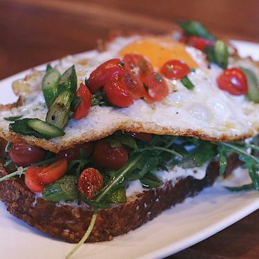 Burrata toast with grilled asparagus, cherry tomato, tarragon, arugula and fried egg at République