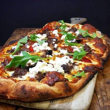 Pizza with mozzarella cheese, ricotta, peperonata, arugula, and short ribs at Farm Shed Dinners