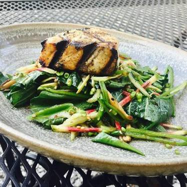 Grilled escolar with snap peas, bok choy, shiitake mushrooms, watermelon radishes tossed in a sesame kumquat dressing at Boucherie