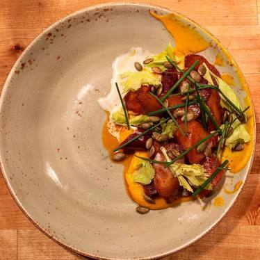 Carrots with carrot purée, ancho butter, cultured cream, and toasted pepitas  at Puritan & Co.