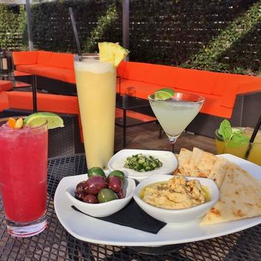 Cocktails with green and black olives, tzatziki sauce, hummus and pita chips at Rosemont