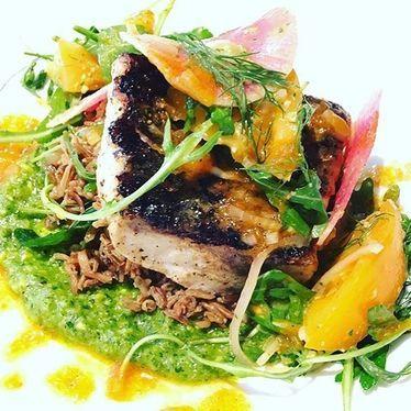 Atlantic Striped Bass w/ wild rice, pesto, watermelon radish, tomatoes, & fresh herbs at The Kitchen