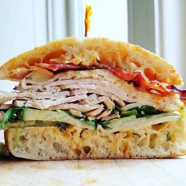 Turkey sandwich with cucumber, chipotle aioli, Swiss cheese, bacon, and arugula on ciabatta  at Dirty South Deli