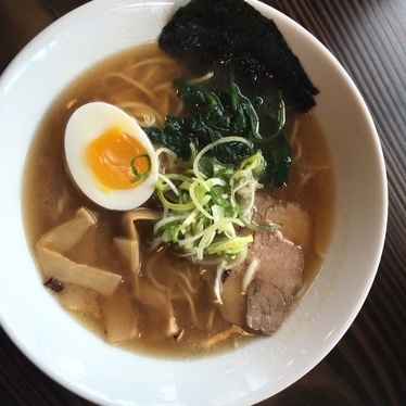 Bowl of ramen with soft-boiled egg, greens, thick noodles and pork at Marukin Ramen