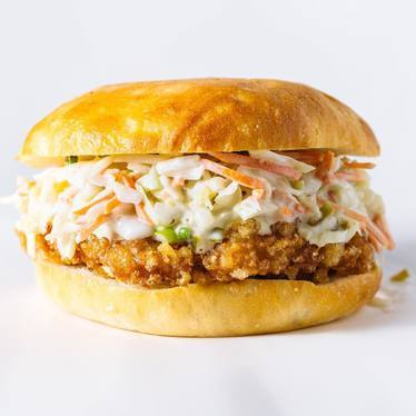 Fried chicken burger with slaw, honey-mustard dressing and pickled jalapeños. at Locol