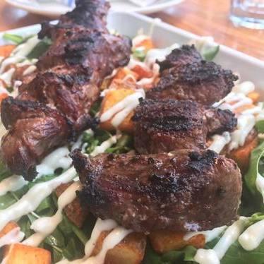 Grass-fed beef skewer, patatas bravas, lemon-garlic aioli at The Hungry Pigeon