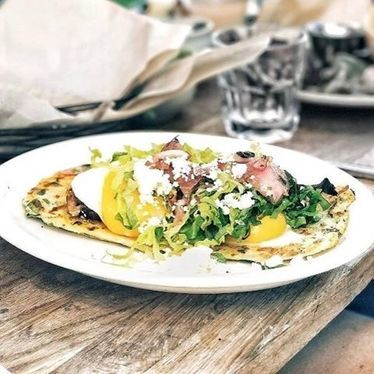 Huarache, spinach, oaxaca cheese, brisket, fried eggs, pickled onion at El Techo de Lolinda