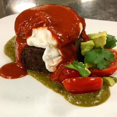 Cilantro lime black bean cake, poached local duck egg, guajillo pepper crema, roasted garlic and poblano sauce at Oasthouse Gastropub