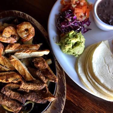 Shrimp and chicken fajitas with corn tortillas, purple cabage, guacamole and tomato at Araña Taqueria Y Cantina
