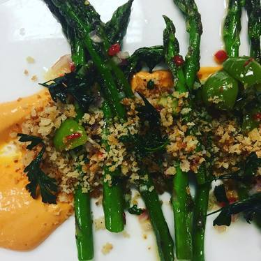 Charred asparagus, Calabrian chili, castelvetrano olive, romesco, toasted breadcrumbs, fried parsley at Crossroads Chapel Hill